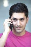 Schließen Sie herauf das Porträt des jungen Mannes sprechend am Telefon lizenzfreie stockbilder