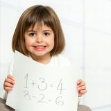 Nettes Mädchen, das Mathesummen auf Papier zeigt. Stockfoto