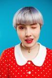 Schließen Sie herauf das schöne dollish Mädchen des Porträts mit dem kurzen hellvioletten Haar, das rotes Kleid blinzelnd über bl Lizenzfreie Stockfotografie