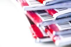 Schließen Sie herauf das Teil des Barcodes auf der roten Zeitschrift, die mit Weiß stapelt Stockbilder