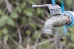 Schließen Sie herauf den Hahn des Metallblauen Wassers, der im Waldwasser shorta alt ist Stockfotos