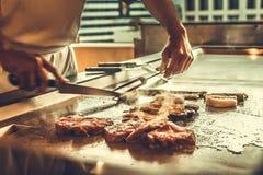 Schließen Sie herauf den Handchef, der Rindfleischsteak und -gemüse auf heißer Wanne kocht Lizenzfreie Stockbilder