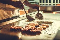 Schließen Sie herauf den Handchef, der Rindfleischsteak und -gemüse auf heißer Wanne kocht, Stockfoto