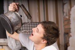Schließen Sie herauf den jungen Mann, der vom Weinlese-Kessel trinkt Stockbilder