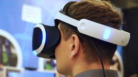 Schließen Sie herauf den jungen Mann, der VR-Kopfhörer verwendet, der Drehenkopf 4k des Spiels der virtuellen Realität spielt stock footage