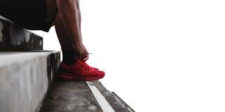 Schließen Sie herauf den Läufer, der Spitze auf den Schritten bindet, lokalisiert auf weißem Hintergrund mit Kopienraum, gesunder Lizenzfreie Stockfotos