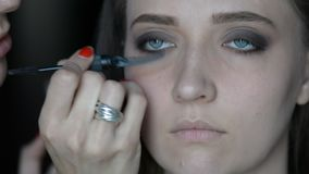 Schließen Sie herauf den Make-upkünstler, der auf Make-up auf vorbildlichen ` s Augen und Brauen mit cosmeticmacro Bild einer rot stock footage