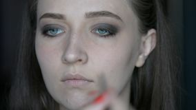 Schließen Sie herauf den Make-upkünstler, der auf Make-up auf vorbildlichen ` s Augen und Brauen mit cosmeticmacro Bild einer rot stock video footage
