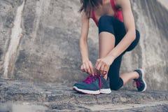 Schließen Sie herauf den niedrigen Winkel der jungen sportlichen Frau und Spitzee des Laufens binden lizenzfreie stockfotos
