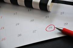 Schließen Sie herauf den roten Kreis, der auf Datum 28 markiert wird stockfoto