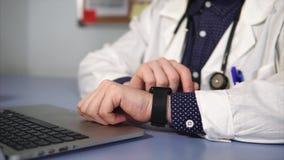 Schließen Sie herauf den Schuss von Doktor intelligente Uhr auf seiner Hand tragend, die in seinem Kabinett arbeitet stock footage