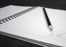 Schließen Sie herauf den schwarzen hölzernen Bleistift, der auf einem gewundenen Notizbuch liegt stockfotografie