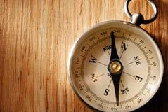 Schließen Sie herauf den Weinlese-Kompass, der auf Holztisch liegt Stockfotografie