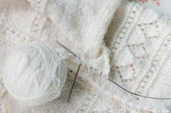 Schließen Sie herauf Detail der weiße Wolle gesponnener Handwerk Knitbabystrickjackendesignbeschaffenheit und -schlaufe Stockfoto