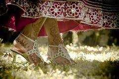 Schließen Sie herauf die Ansicht der hindischen Braut gemalt die Füße, die in Garten tanzen stockfotografie