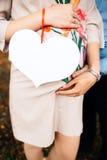 Schließen Sie herauf die Ansicht, die das schwangere glückliche Paar erwartet, das ein leeres weißes Brett in Form des Herzens hä Stockbilder
