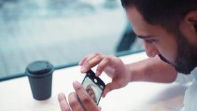 Schließen Sie herauf die Ansicht eines Geschäftsmannes in einem café und einige bewegliche Fotos seines Frühstückskaffees und -h stock video