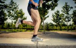 Schließen Sie herauf die athletischen Beine des jungen Mannes laufend in Stadtpark mit Bäumen auf übendem gesundem Lebensstil des Stockfoto