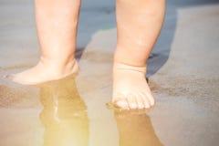 Schließen Sie herauf die Babyfüße, die mit Sand auf dem Strand bei Sonnenuntergang spielen Stockfoto