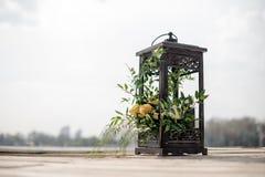 Schließen Sie herauf die Eisenlaterne, die mit tropischen Blumen als Hochzeitsdekor auf der Flussbank verziert wird Lizenzfreie Stockfotografie