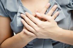 Schließen Sie herauf die Frau, welche die Schmerz- in der Brustbrustschmerz hat Stockfotos