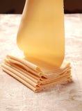 Schließen Sie herauf die frischen flachen Teigwaren, die durch Teigwaren-Rolle gemacht werden Stockfoto