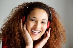 Schließen Sie herauf die glückliche junge Afroamerikanerfrau, die Musik mit Kopfhörern lächelt und hört lizenzfreies stockbild