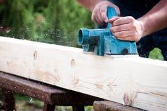 Schließen Sie herauf die Hände des Tischlers arbeitend mit elektrischem Hobel auf hölzerner Planke lizenzfreies stockbild