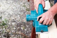 Schließen Sie herauf die Hände des Tischlers arbeitend mit elektrischem Hobel auf hölzerner Planke stockfotos