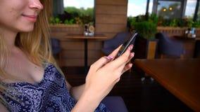 schließen Sie herauf die Hände, die Mitteilung durch Smartphone am Café schreiben Lizenzfreie Stockbilder