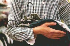 Schließen Sie herauf die Hand, die Bündel neue Kleidung hält, um im Speicher, ein Einkaufsverkaufskonzept zu kaufen stockfotografie