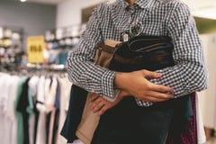 Schließen Sie herauf die Hand, die Bündel neue Kleidung hält, um im Speicher, ein Einkaufsverkaufskonzept zu kaufen stockbild