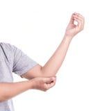 Schließen Sie herauf die Hand der Frau, die ihren Ellbogen lokalisiert auf Weiß hält winkelstück Stockbilder