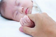 Schließen Sie herauf die Hand des Elternteils Hand des schlafenden Kindes umklammernd Stockfotos