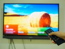 Schließen Sie herauf die Hand, die Fernsehen Fernsteuerungs hält Lizenzfreie Stockbilder
