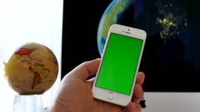 Schließen Sie herauf die Hand, die grüne Schirm iphone und das Kugelspinnen hält stock video footage