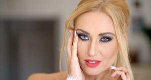 Schließen Sie herauf die herrliche blonde Frau, die ihr Gesicht berührt stock video footage
