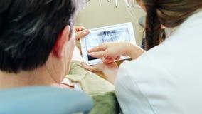 Schließen Sie herauf die hintere Ansicht des Zahnarztes Röntgenstrahl von Zähnen auf Tablette zeigend dem Patienten stock video