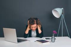 Schließen Sie herauf die junge glückliche Geschäftsfrau des Porträts, die an ihrem Schreibtisch in einem Büro sitzt an einer Lapt Lizenzfreies Stockbild