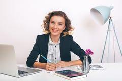 Schließen Sie herauf die junge glückliche Geschäftsfrau des Porträts, die an ihrem Schreibtisch in einem Büro sitzt an einer Lapt Stockfotografie