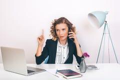 Schließen Sie herauf die junge glückliche Geschäftsfrau des Porträts, die an ihrem Schreibtisch in einem Büro sitzt an einer Lapt Lizenzfreies Stockfoto