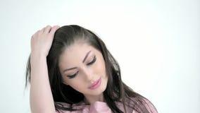 Schließen Sie herauf die junge schöne kaukasische Frau, die Kamera betrachtet und korrigiert Frisur stock footage