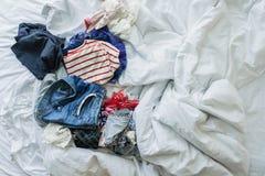 Schließen Sie herauf die Kleidung und Zubehör, die auf ungemachtes Bett geworfen werden Lizenzfreie Stockbilder