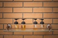 Schließen Sie herauf die Konditionierungsshampoo- und Duschcremeflaschen, die auf Glasregal mit Backsteinmauer in den Hintergrund stockbild