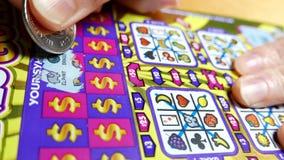 Schließen Sie herauf die Leute, die Lottoschein verkratzen stock video footage