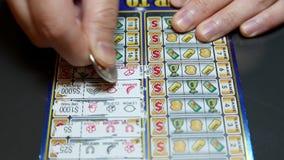 Schließen Sie herauf die Leute, die Lottoschein verkratzen stock footage