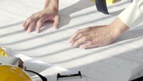 Schließen Sie herauf die männlichen Hände, die Pläne auf der weißen Tabelle ausbreiten, die durch die Sonne im modernen Büro bele stock video