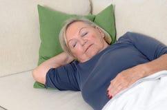 Schließen Sie herauf die Mitte gealterte blonde Frau, die auf Couch stillsteht Lizenzfreie Stockbilder