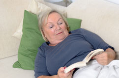 Schließen Sie herauf die Mitte gealterte blonde Frau, die auf Couch stillsteht Stockfotografie