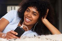 Schließen Sie herauf die schöne junge afrikanische Frau, die auf dem Boden liegt, der Musik mit Kopfhörern und Handy hört Stockfoto